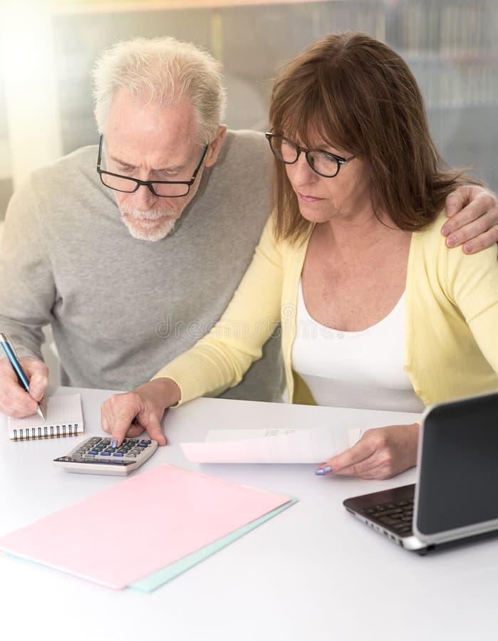 Couples supérieurs vérifiant le document financier, effet de la lumière photographie stock libre de droits