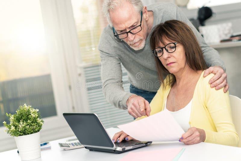 Couples supérieurs vérifiant le document financier, effet de la lumière images stock