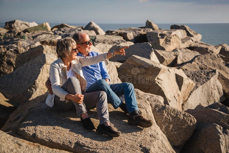 Couples sup?rieurs actifs marchant sur les roches ensoleill?es par la mer images stock