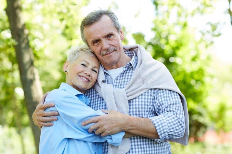 Couples sup?rieurs heureux embrassant en parc images libres de droits