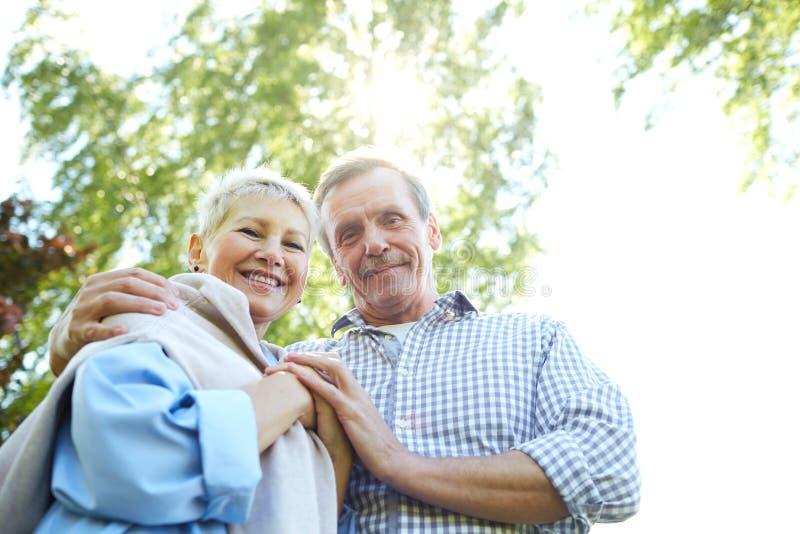 Couples sup?rieurs heureux marchant en parc images stock