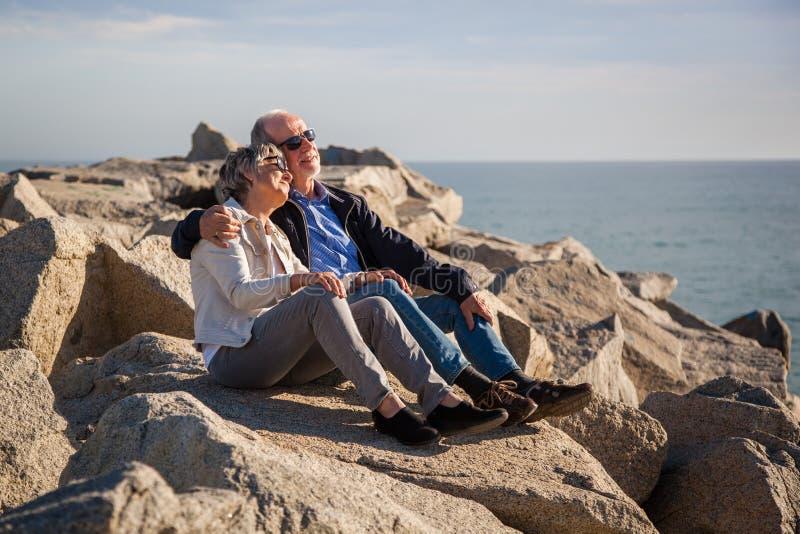 Couples sup?rieurs heureux se reposant sur des roches par la mer image stock