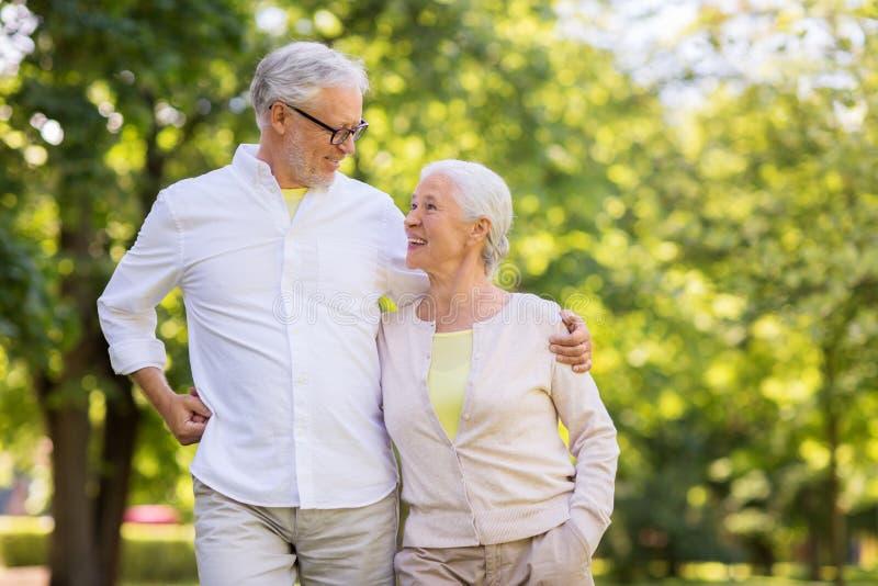 Couples sup?rieurs heureux ?treignant au parc d'?t? photographie stock libre de droits