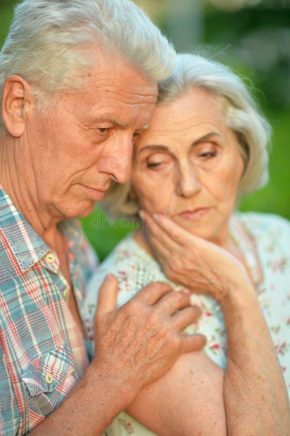 Couples sup?rieurs malheureux posant en parc d'?t? images libres de droits