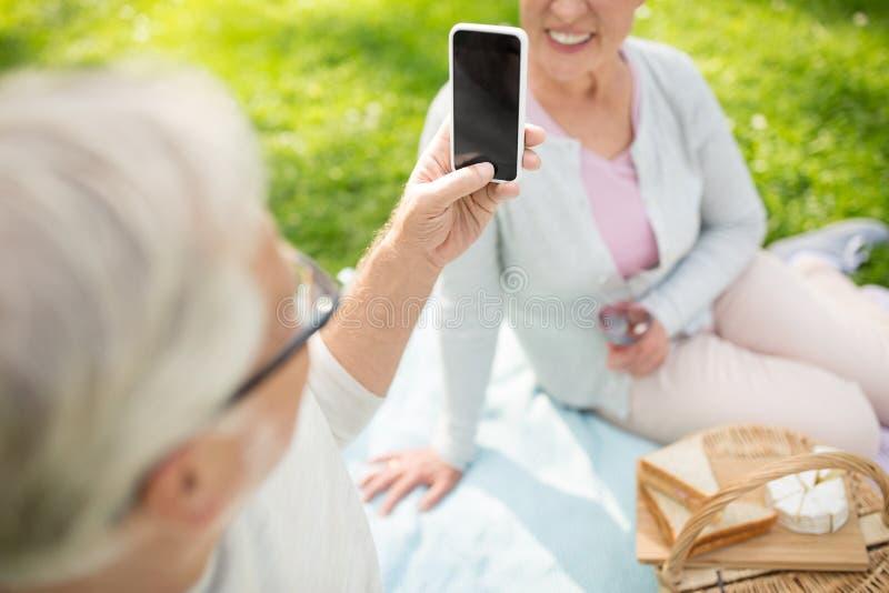Couples sup?rieurs prenant la photo par le smartphone au parc image stock