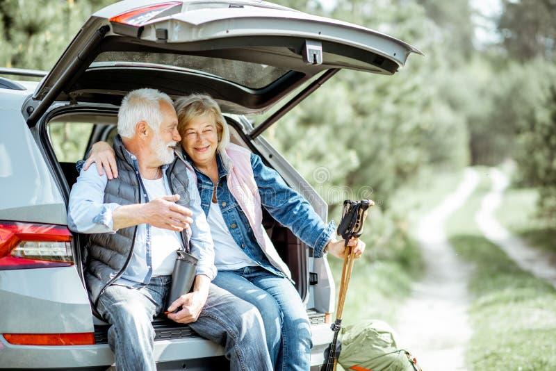 Couples sup?rieurs voyageant en voiture photos stock