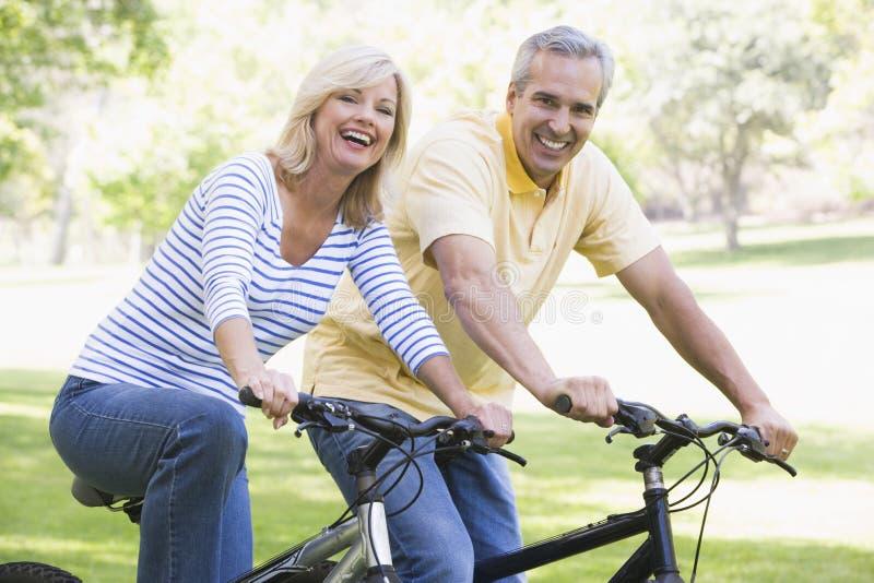 Couples sur des vélos souriant à l'extérieur photo stock