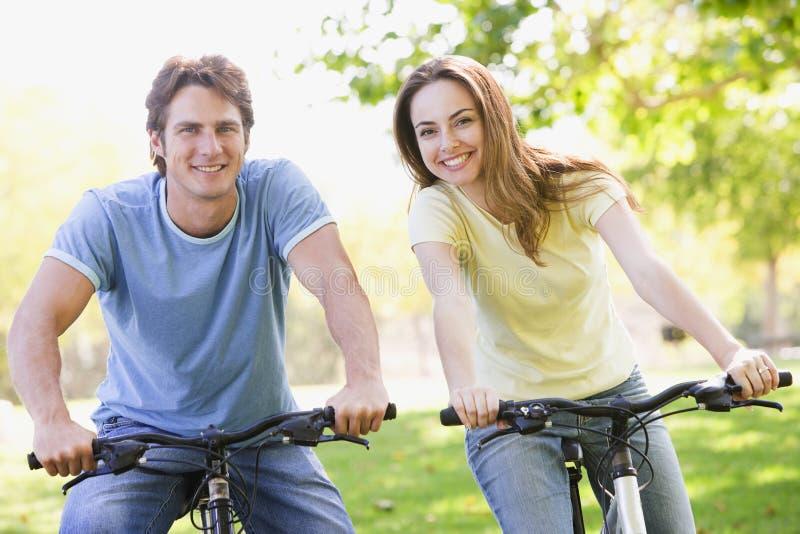 Couples sur des vélos souriant à l'extérieur photographie stock