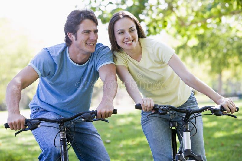 Couples sur des vélos souriant à l'extérieur photo libre de droits
