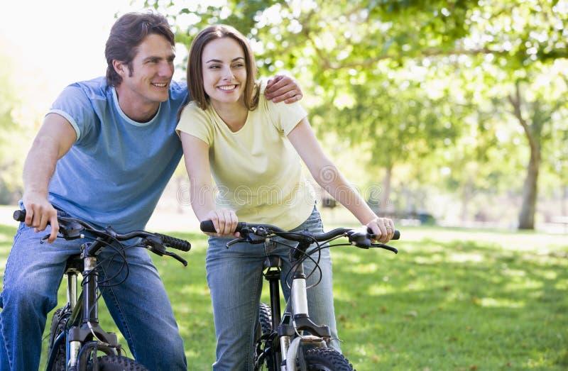 Couples sur des vélos souriant à l'extérieur images libres de droits