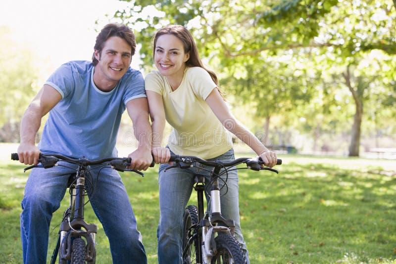 Couples sur des vélos souriant à l'extérieur image stock