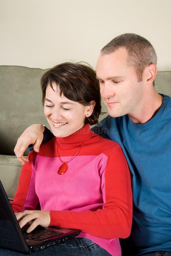 Couples sur l'ordinateur portatif images stock