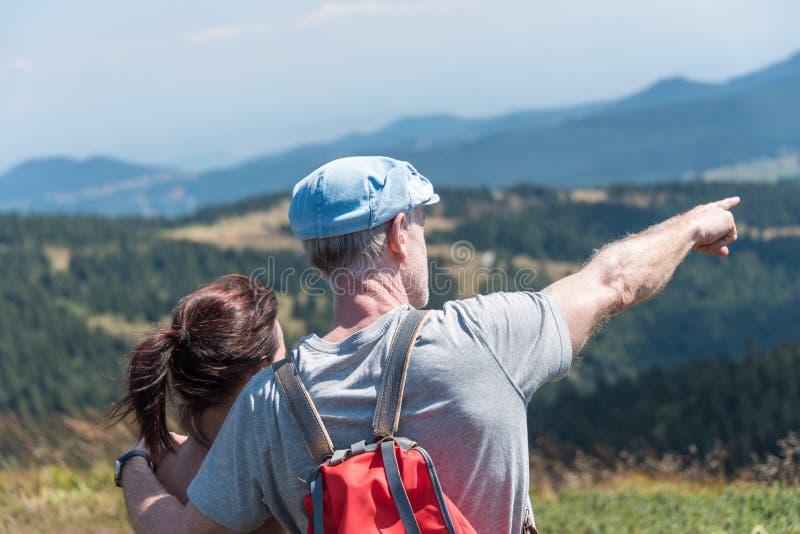 Couples sur la hausse regardant le paysage image stock