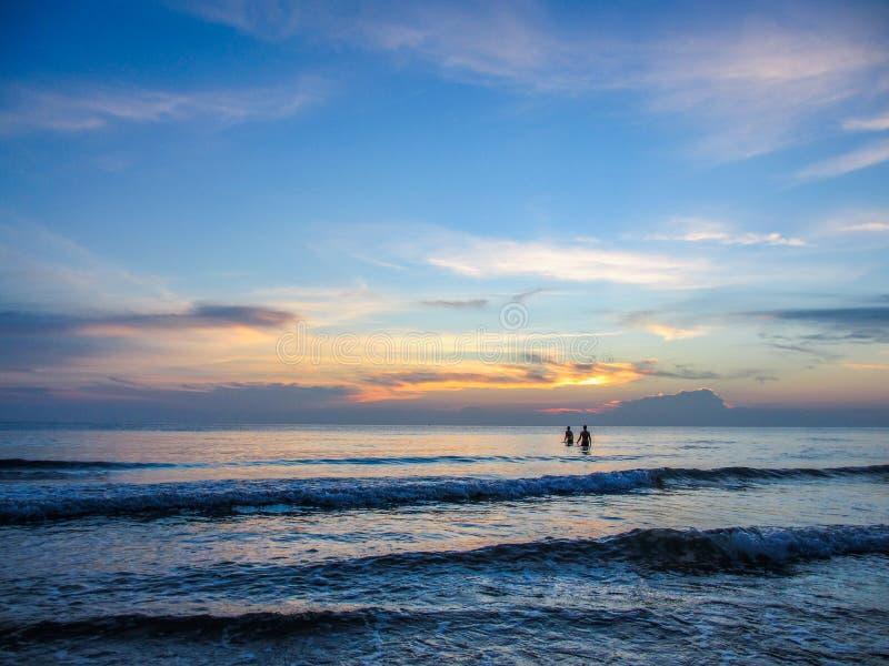 Couples sur la mer de coucher du soleil photos stock