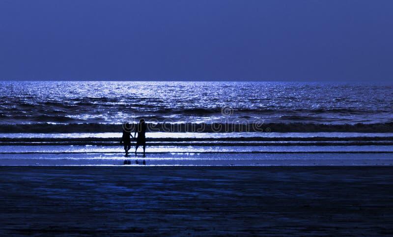 Couples sur la plage la nuit de lumière de lune photo stock