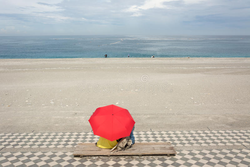 Couples sur la plage sous le parapluie photos stock