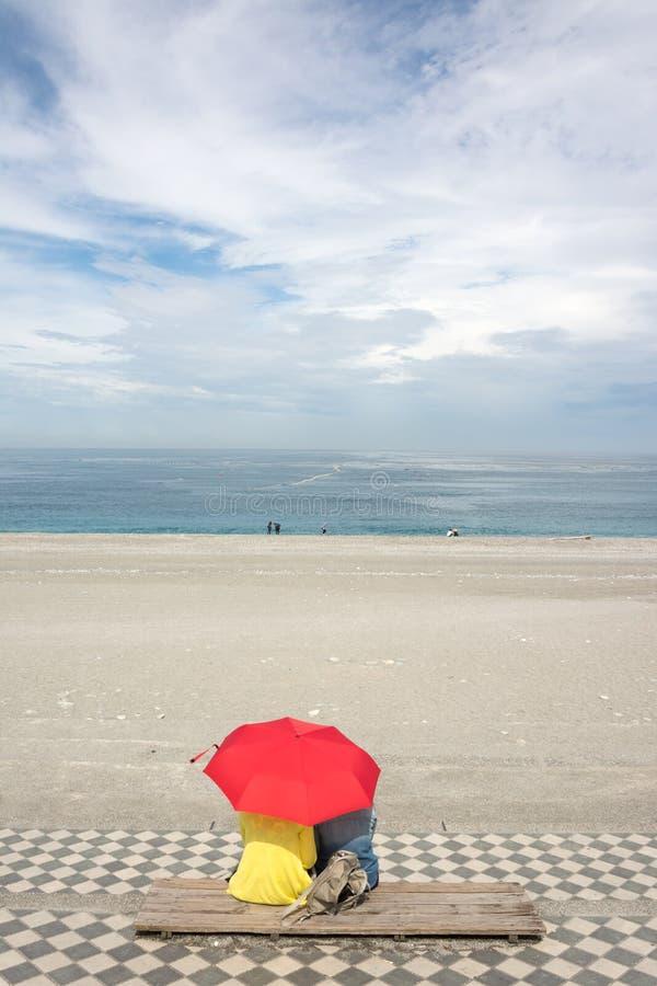 Couples sur la plage sous le parapluie image stock