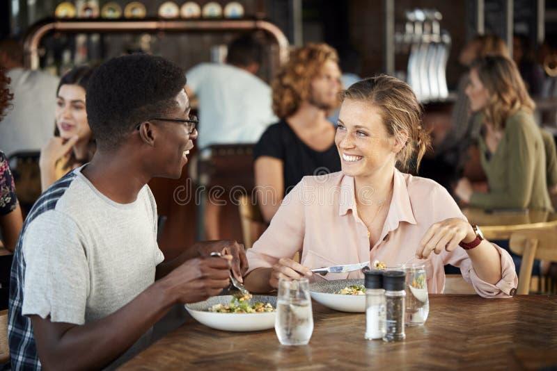 Couples sur la réunion de date pour les boissons et la nourriture faisant un pain grillé dans le restaurant photo libre de droits