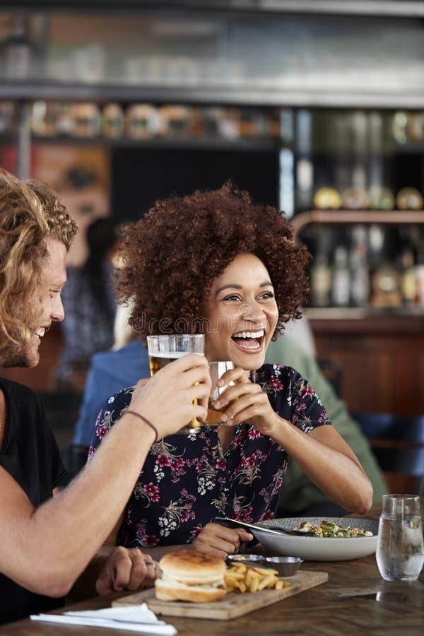 Couples sur la réunion de date pour les boissons et la nourriture faisant un pain grillé dans le restaurant photos libres de droits