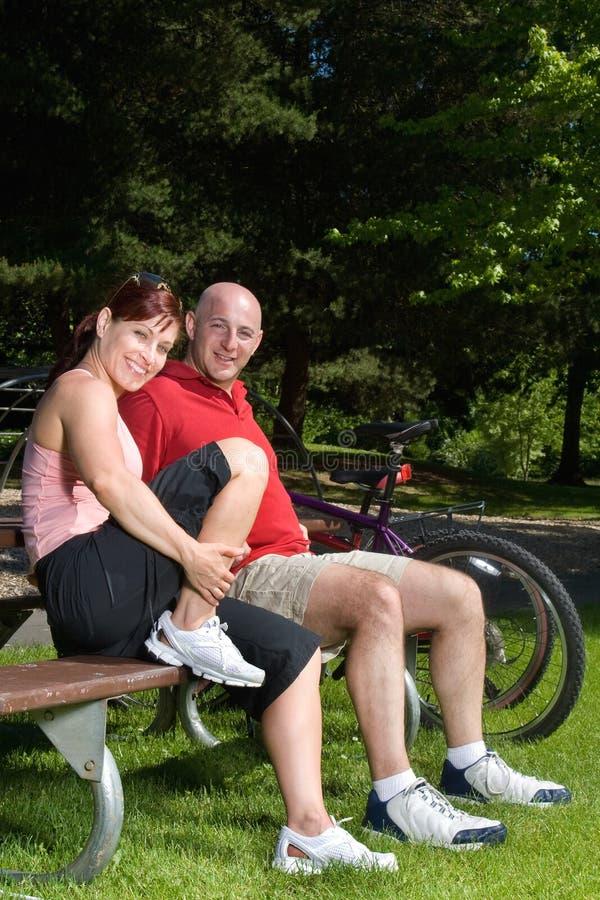 Couples sur le banc de stationnement - verticale images stock