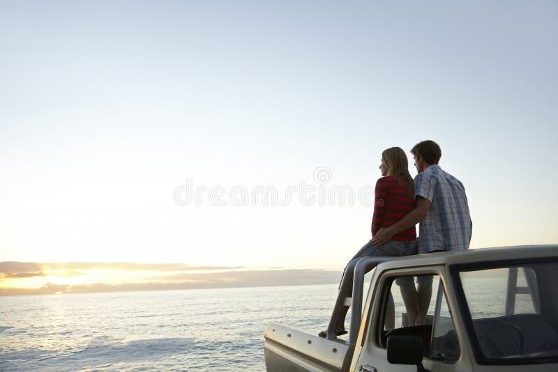 Couples sur le camion de collecte garé en Front Of Ocean images stock
