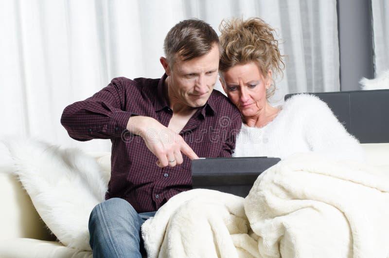 Couples sur le divan regardant sur le comprimé photos stock