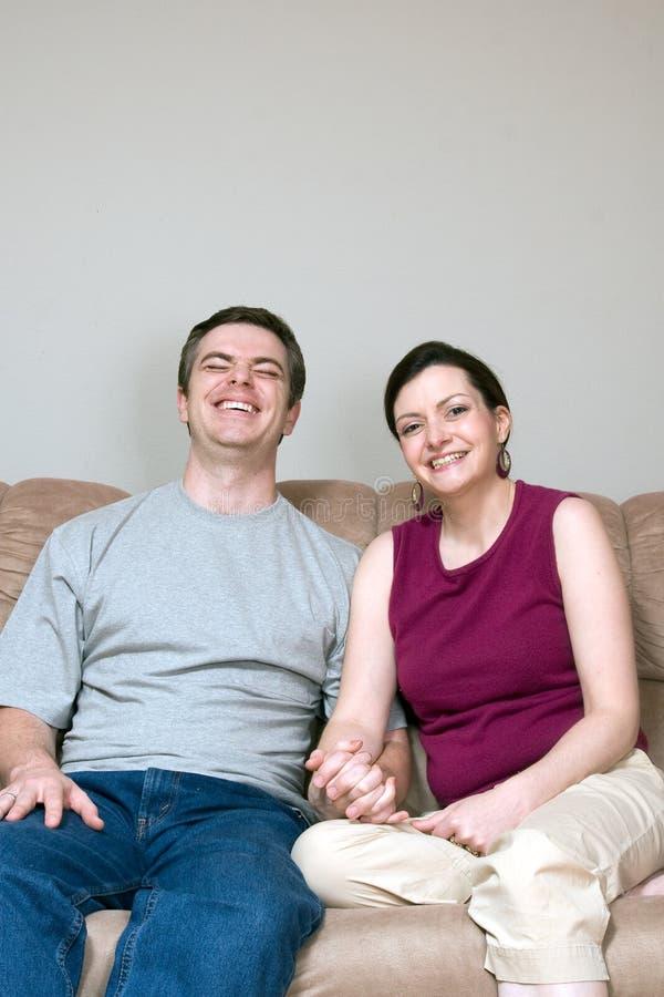 Couples sur le divan riant - verticale photos stock