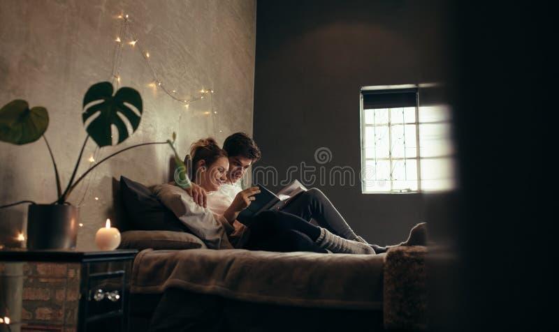 Couples sur le livre de lecture de lit photos libres de droits