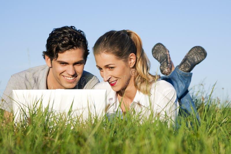 Couples sur le pré utilisant Wi-Fi pour l'Internet photos libres de droits