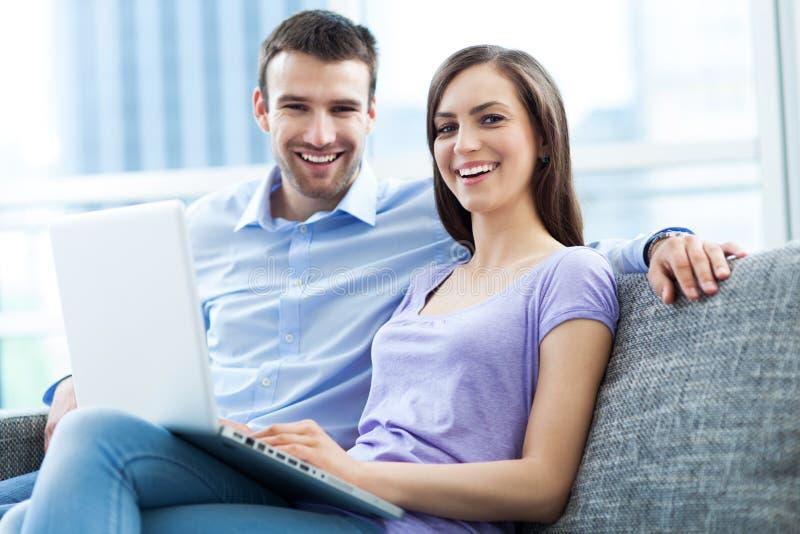 Couples sur le sofa avec l'ordinateur portable photo stock