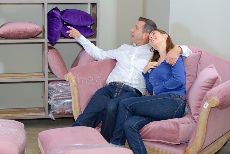 Couples sur le sofa dans la salle d'exposition photos libres de droits
