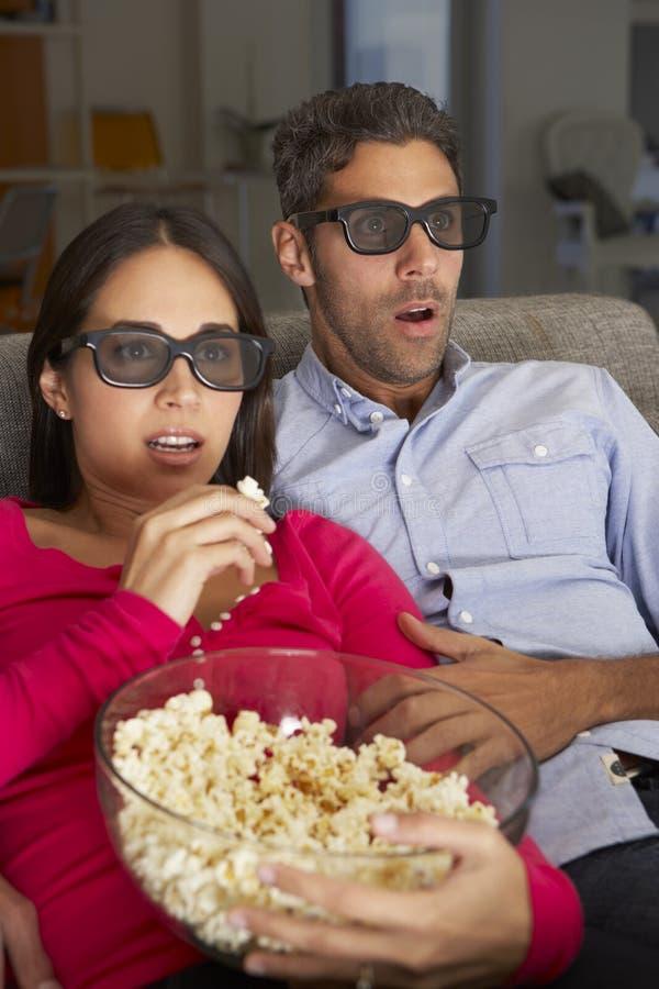 Couples sur Sofa Watching TV portant les lunettes 3D mangeant du maïs éclaté image stock