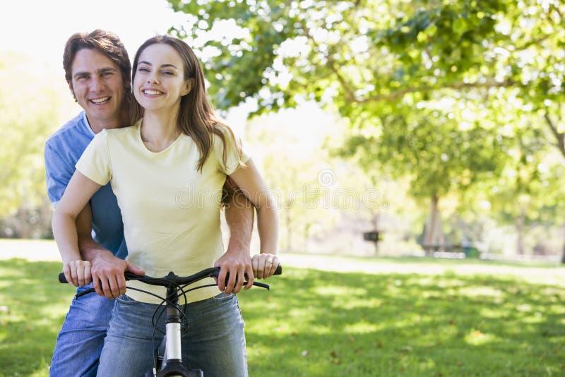 Couples sur un vélo souriant à l'extérieur photographie stock libre de droits