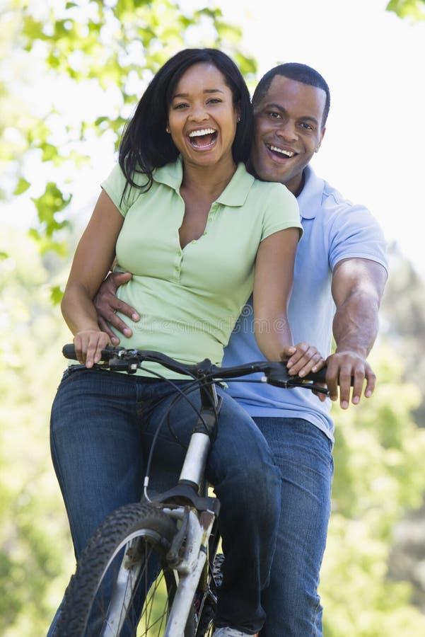 Couples sur un vélo souriant à l'extérieur photographie stock