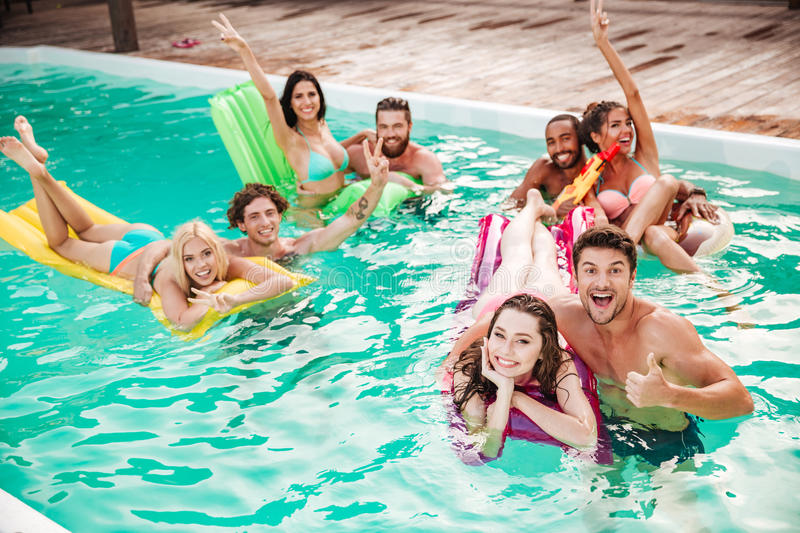 Couples swimming in pool and having fun stock photos