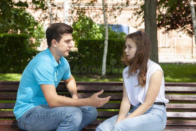 Couples ?t?s en conflit ne parlant pas entre eux assis sur un banc en bois en parc photos libres de droits