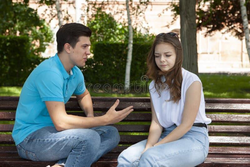 Couples ?t?s en conflit ne parlant pas entre eux assis sur un banc en bois en parc images libres de droits