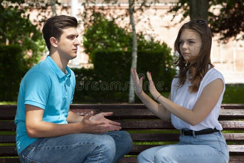 Couples ?t?s en conflit ne parlant pas entre eux assis sur un banc en bois en parc photo libre de droits