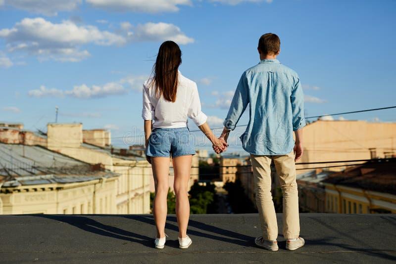 Couples tenant des mains sur le toit image stock