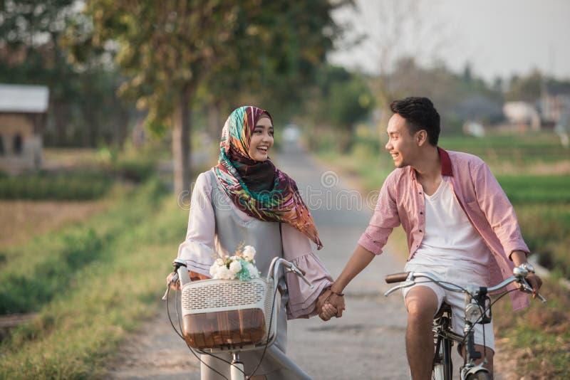 Couples tenant des mains tandis que tour un vélo images stock