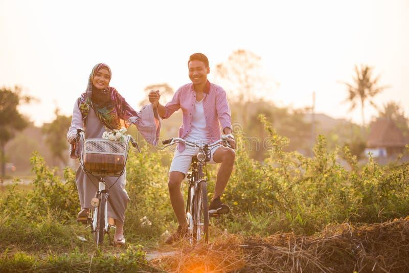 Couples tenant des mains tandis que tour un vélo photographie stock