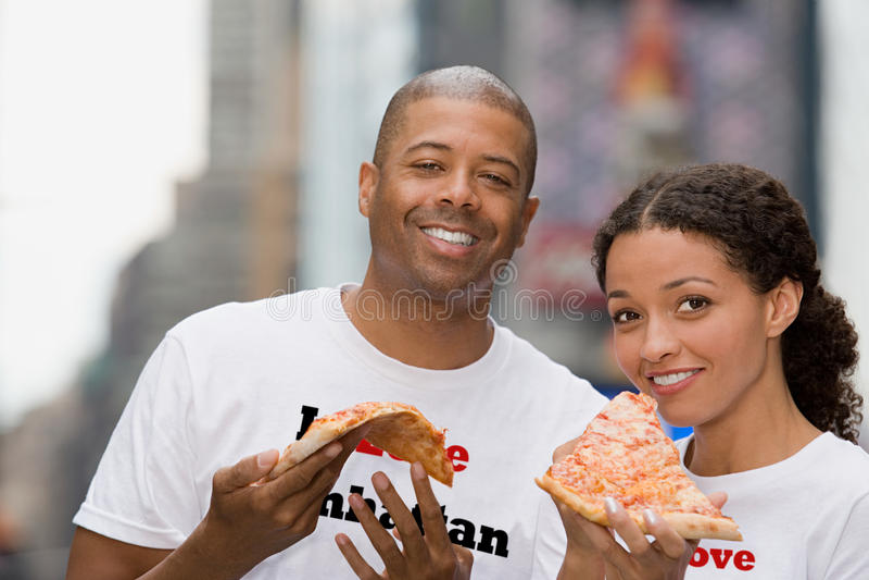 Couples tenant la pizza image stock