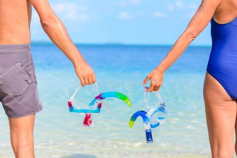Couples tenant le masque naviguant au schnorchel à disposition Vue arrière, oarts de corps, position adulte de mer de turquoise,  photos libres de droits