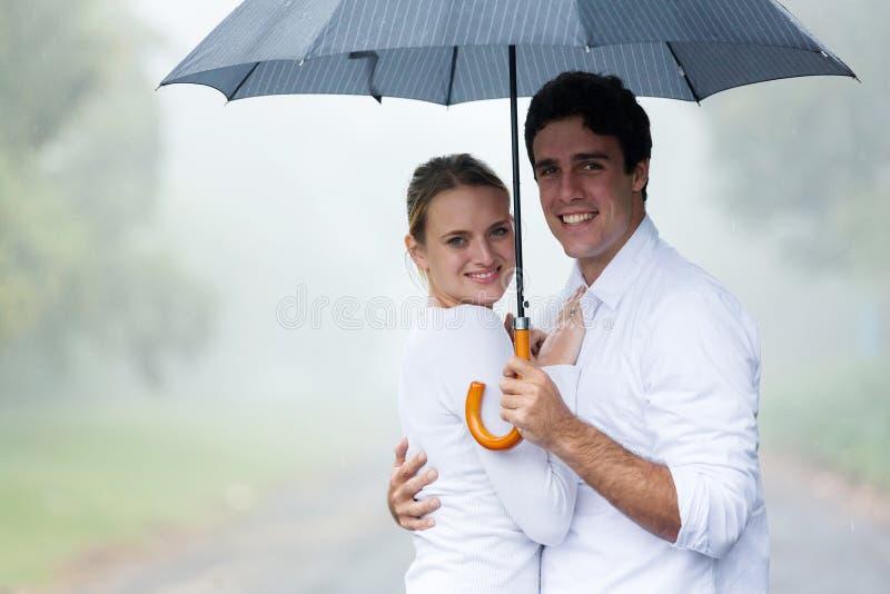 couples tenant le parapluie image stock