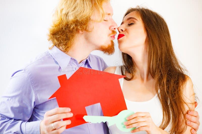 Couples tenant les symboles de papier d'immobiliers images stock