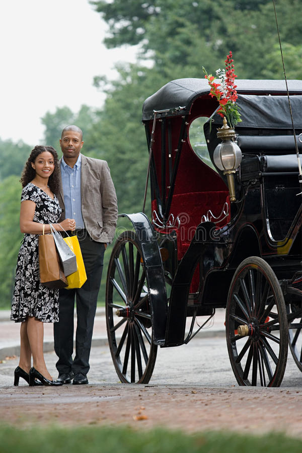 Couples tenus à côté du chariot hippomobile photo stock