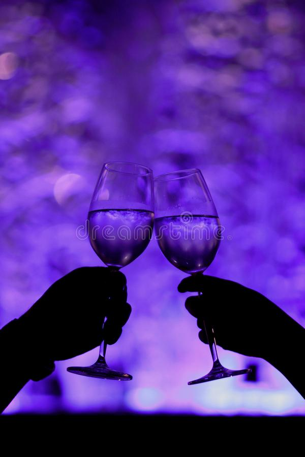 Couples Toast in Romantic Moments. Silhouette of two glasses of male female couples drink in romantic moments stock photography