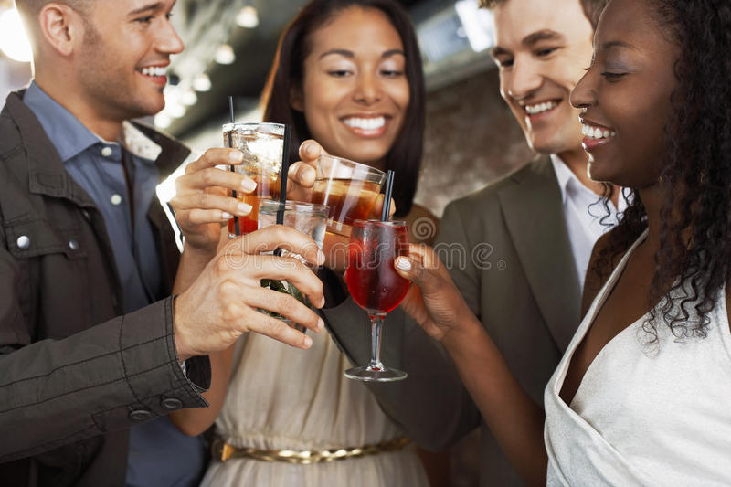 Couples Toasting Drinks At Bar. Two happy multiethnic couples toasting drinks at the bar stock image