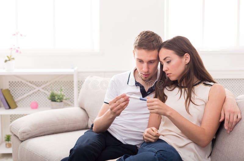 Couples tristes après l'espace de copie de résultat d'essai de grossesse photos stock