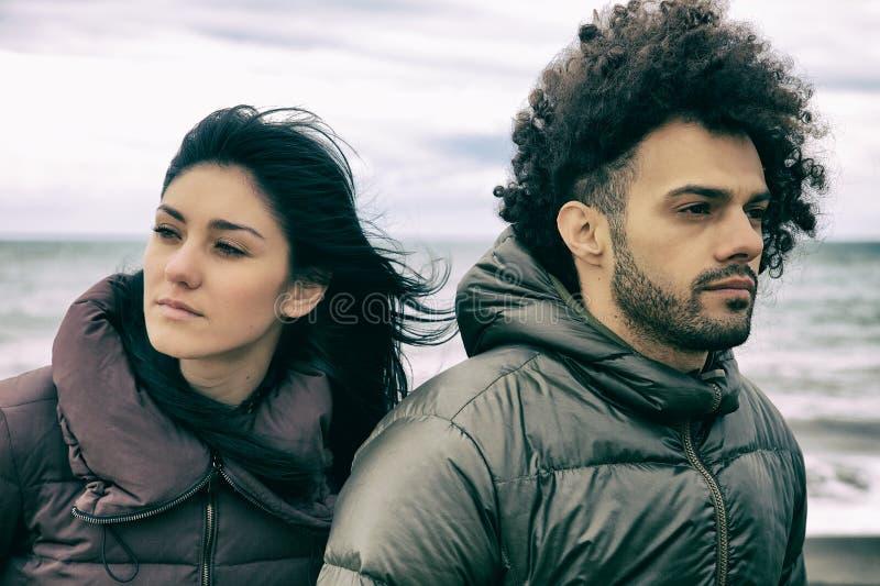 Couples tristes devant la pensée de plage photographie stock libre de droits